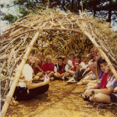 students in hand-built hut